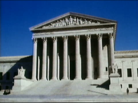 1964 low angle medium shot US Supreme Court building with blue sky in background / Washington DC