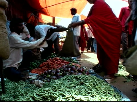 low angle medium shot vendor selling produce to woman at market - banknote stock videos & royalty-free footage