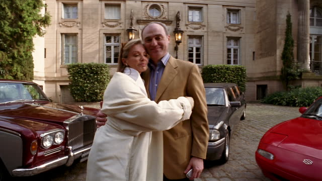 Low angle medium shot wealthy mature woman and man hugging in front of luxury cars + mansion / looking at CAM