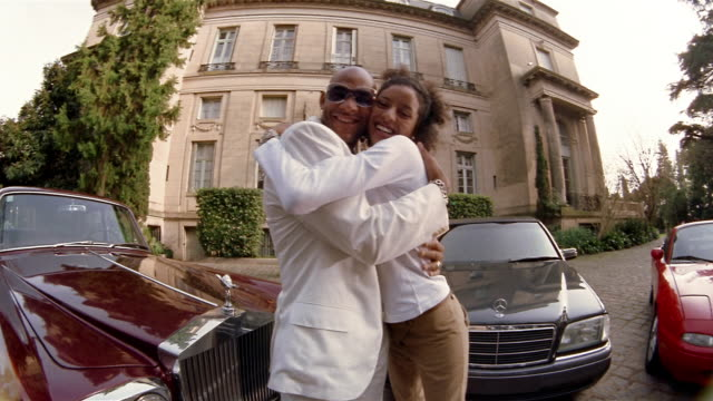 low angle medium shot wealthy young couple hugging and smiling at cam in front of cars + mansion / showing off jewelry - rolls royce stock videos and b-roll footage