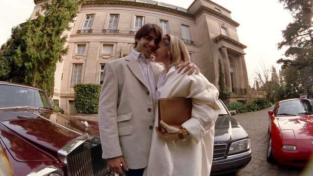 low angle medium shot wealthy young man and older woman nuzzling + smiling at cam in front of cars + mansion - mercedes benz stock videos and b-roll footage