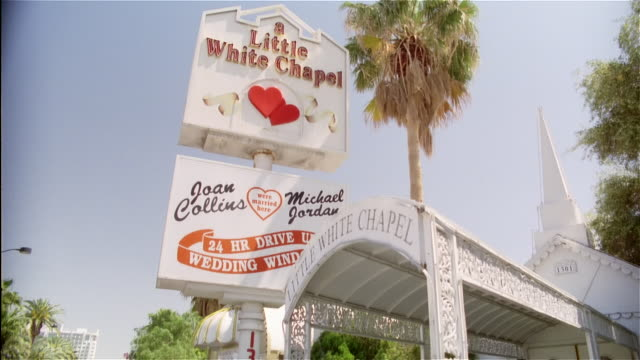 low angle medium shot wedding chapel sign / tilt down bride and groom leaving chapel / kissing and embracing - las vegas stock videos & royalty-free footage