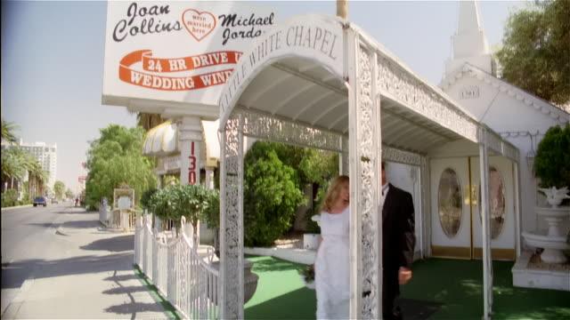 Low angle medium shot wedding chapel sign / tilt down bride and groom leaving chapel / kissing and embracing