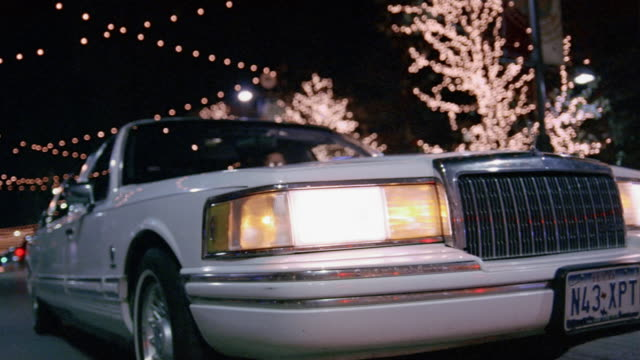 low angle medium shot white limousine passing by camera on street decorated with christmas lights at night - リムジン点の映像素材/bロール