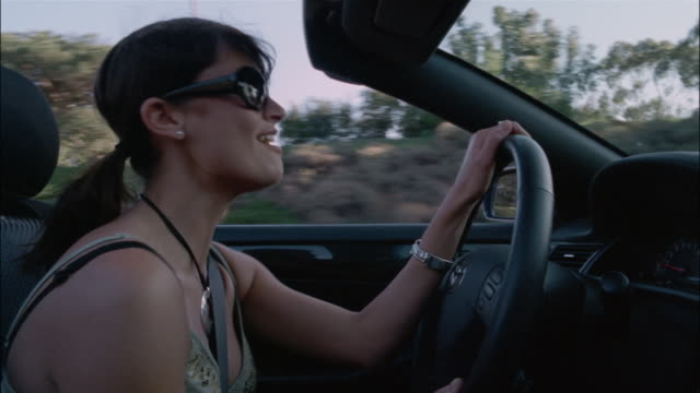 Low angle medium shot woman driving convertible and singing along to radio