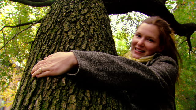 low angle medium shot woman hugging tree/ brooklyn, new york - tree hugging stock videos & royalty-free footage
