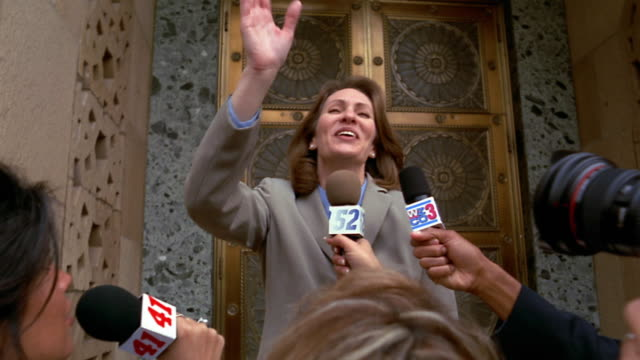 low angle medium shot woman in suit smiling and waving at press conference - press conference stock videos and b-roll footage