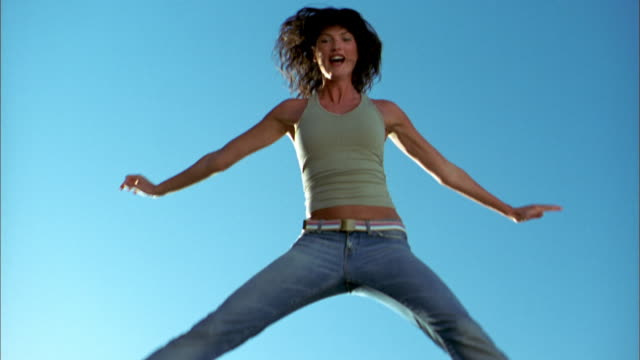 low angle medium shot woman jumping against blue background - farbiger hintergrund stock-videos und b-roll-filmmaterial