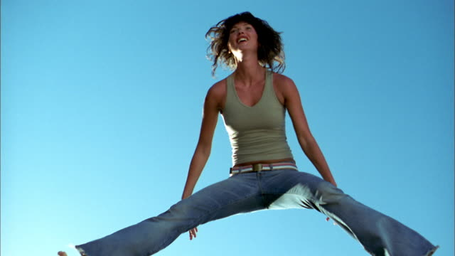 Low angle medium shot woman jumping and slapping her legs against blue background