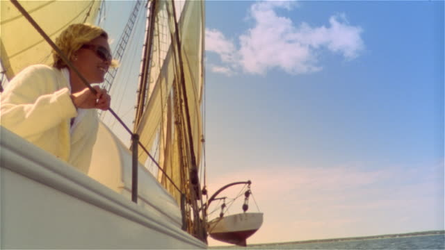 low angle medium shot woman looking out at sea over ship's rail - only mid adult women stock videos & royalty-free footage
