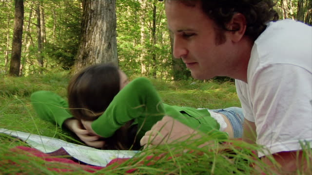 low angle medium shot woman lying on back in grass and stretching / man lying next to her reading map - lying on back stock videos & royalty-free footage