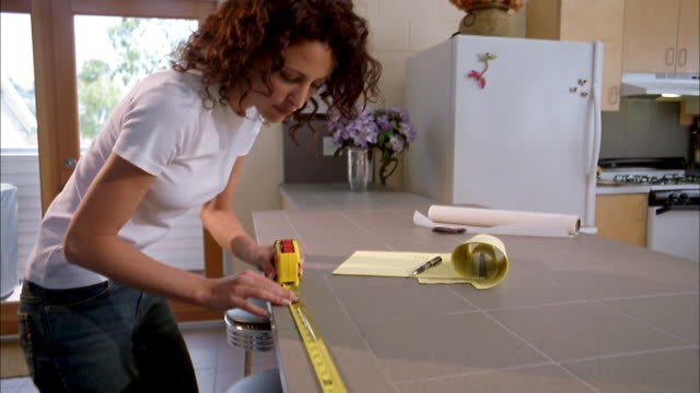 vidéos et rushes de low angle medium shot woman measuring length of counter top w/tape measure and writing on notepad - tape measure