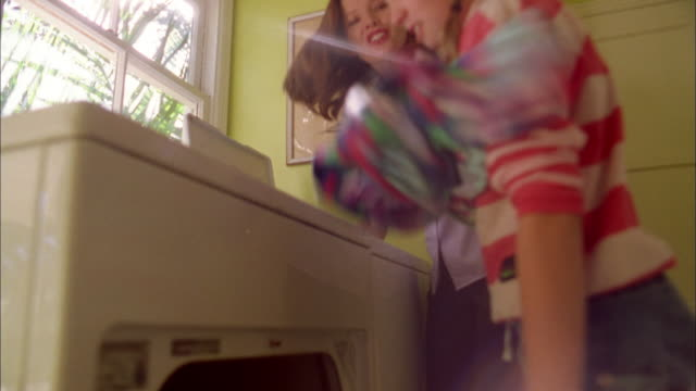low angle medium shot woman passing clothes from washer to young girl / girl loading clothes in dryer - washing stock videos & royalty-free footage