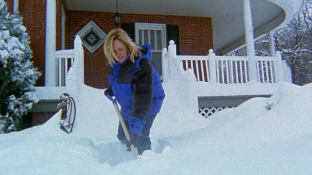 vídeos y material grabado en eventos de stock de low angle medium shot woman shoveling snow on front walk - excavar