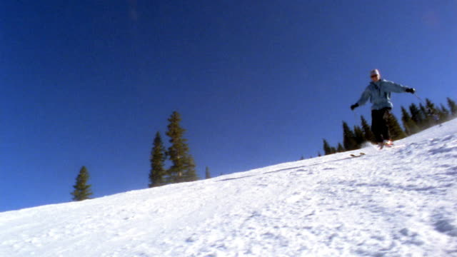 vídeos de stock, filmes e b-roll de low angle medium shot woman skiing downhill w/pine trees in background / colorado, usa - só uma mulher madura