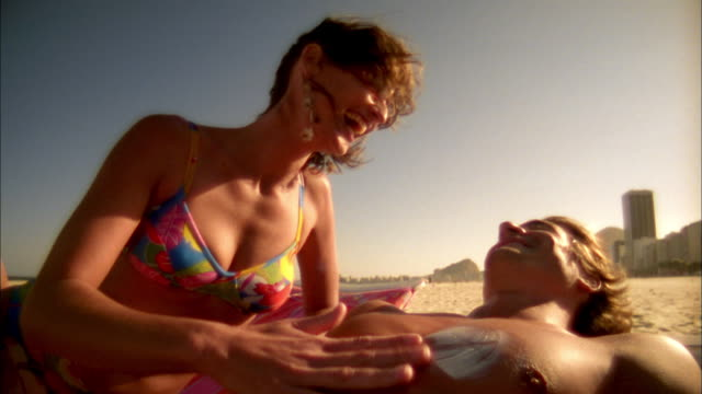 Low angle medium shot woman smiling and rubbing suntan lotion on man's chest
