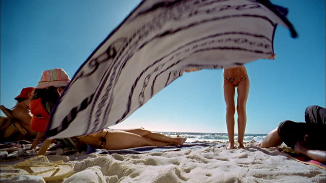 low angle medium shot woman spreading blanket on beach and sunbathing on her stomach - sunbathing stock videos and b-roll footage