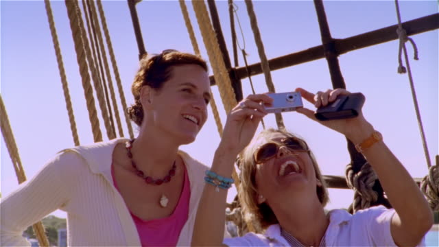 Low angle medium shot woman taking pictures with digital camera aboard tall ship / other woman looking up at mast