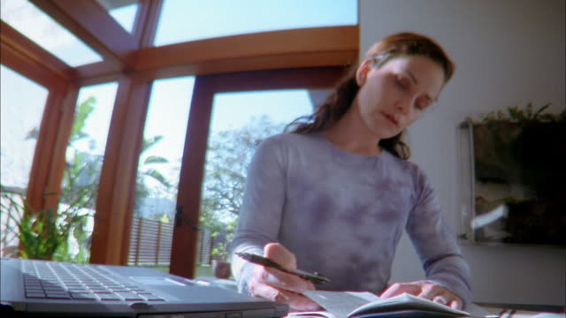 low angle medium shot woman using computer and writing in checkbook to pay bills - scheck stock-videos und b-roll-filmmaterial