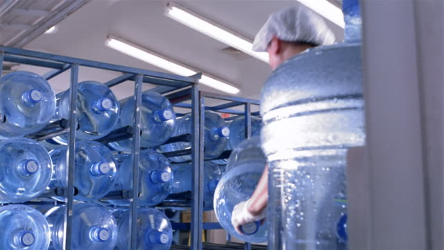 low angle medium shot worker loading water cooler jugs onto rack at water purification plant / san antonio, texas - cooler container stock videos & royalty-free footage