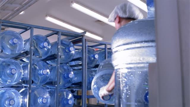 Low angle medium shot worker loading water cooler jugs onto rack at water purification plant / San Antonio, Texas