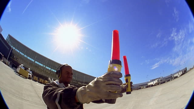 Low angle medium shot worker signaling aircraft at airport