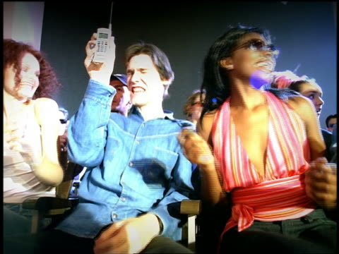 vídeos de stock, filmes e b-roll de low angle medium shot young adults dancing in audience at concert with man in front holding up cell phone - rock moderno