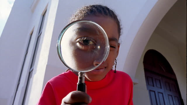 stockvideo's en b-roll-footage met low angle medium shot young black boy looking through magnifying glass - vergrootglas