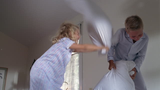 Low angle medium shot young boy and girl having pillow fight on bed / feathers flying / Miami, Florida