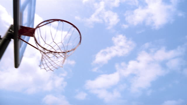 low angle medium shot young boy being lifted up to basketball hoop / boy dropping ball into hoop - basket stock videos & royalty-free footage