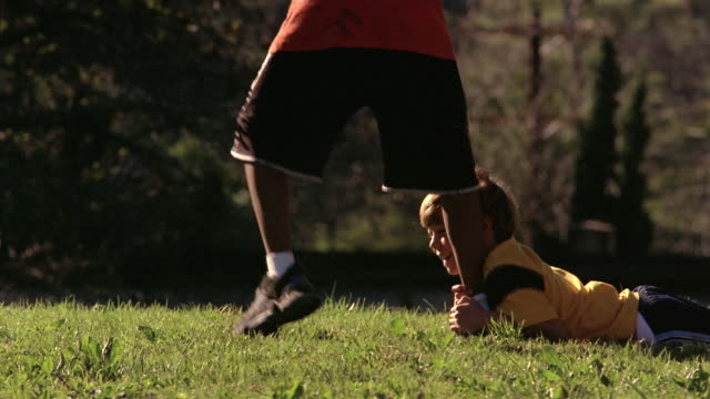 Low angle medium shot young boy holding onto boy's leg and being dragged across the grass
