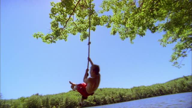 low angle medium shot young boy swinging and jumping into lake from rope - seil stock-videos und b-roll-filmmaterial