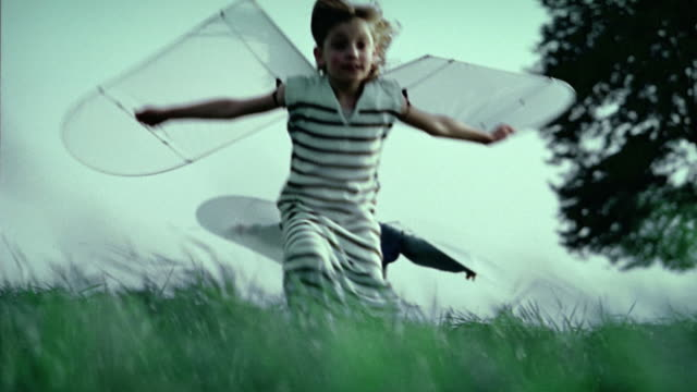 Low angle medium shot young girl and boy running in field with paper wings attached to their arms / Belgium