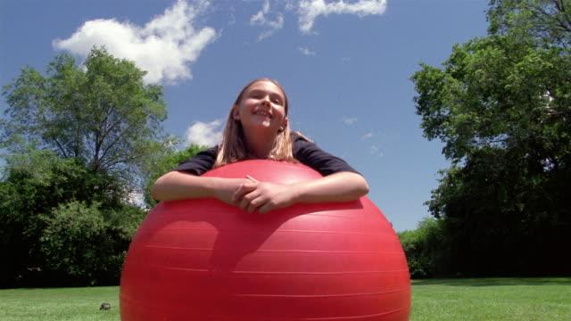 vídeos de stock e filmes b-roll de low angle medium shot young girl bouncing on red inflatable ball with trees in background - saltar para cima e para baixo