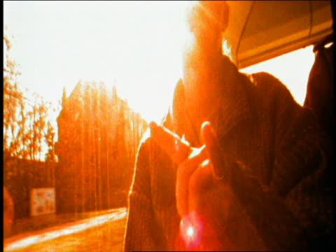 low angle medium shot young man riding bus gesturing and drinking from can on bus / sun in background / munich, germany - tonad bild bildbanksvideor och videomaterial från bakom kulisserna
