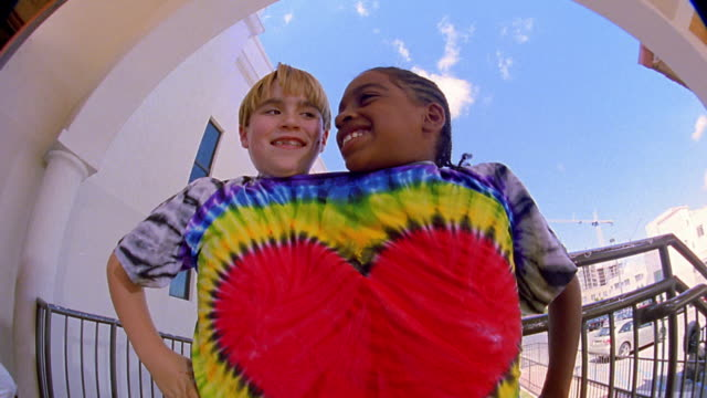 Low angle medium shot young White and Black boys both wearing heart design tie-dyed T-shirt