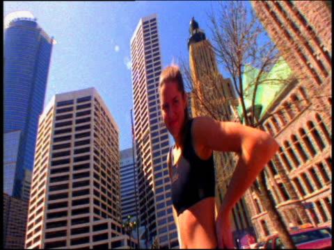 vídeos de stock, filmes e b-roll de low angle medium shot young woman making faces to camera with buildings in background / new york city - só uma mulher de idade mediana