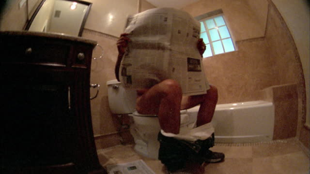 vídeos y material grabado en eventos de stock de low angle medium shot zoom in man on toilet reading newspaper / close up lowering newspaper and looking at cam - hombres desnudos
