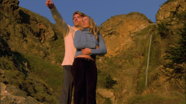 low angle medium shot zoom out couple standing on rocky cliff/ monterey county, california - ragged point stock videos and b-roll footage