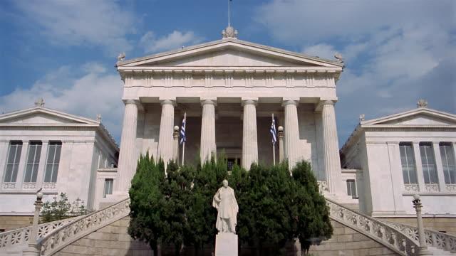 vídeos y material grabado en eventos de stock de low angle medium shot zoom out national library with greek flags in foreground and on top / athens, greece - entabladura