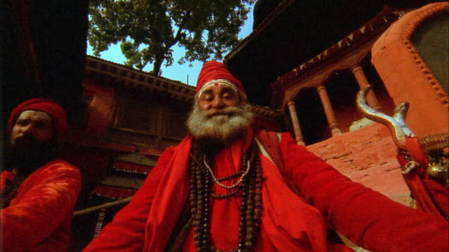 low angle medium shot zoom out senior sadhu holy man sitting in meditation pose with temple in background / kathmandu, nepal - priest stock videos & royalty-free footage