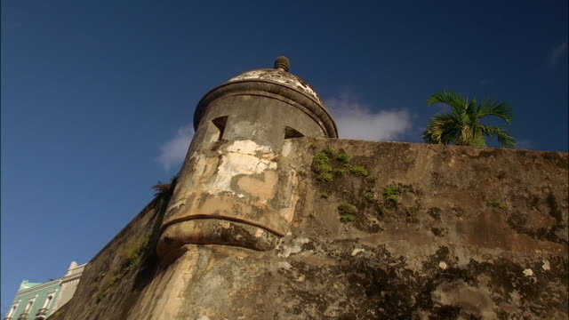 Low angle medium shot zoom out wide shot corner lookout tower of fortified wall of San Cristobal / Old San Juan, Puerto Rico