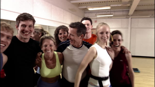 Low angle medium shot zoom portrait of men and women with instructor after step aerobics class / cheering and congratulating each other