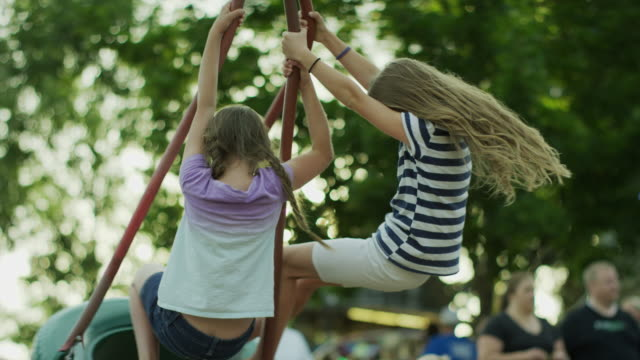 low angle medium slow motion shot of girls playing on tire swing / pleasant grove, utah, united states - tire swing stock videos & royalty-free footage