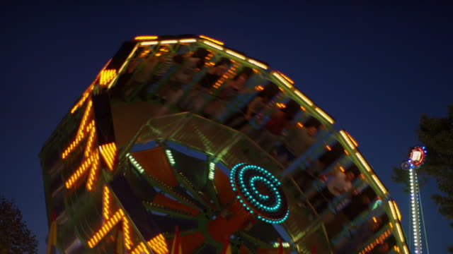 Low angle medium slow motion shot of glowing amusement park rides / Pleasant Grove, Utah, United States