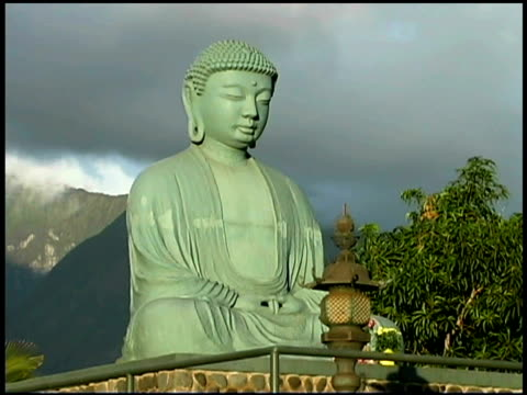 low angle medium view of a buddha statue in a garden. - female likeness stock videos & royalty-free footage