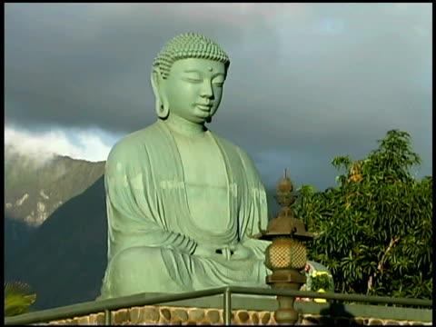low angle medium view of a buddha statue in a garden. - weibliche figur stock-videos und b-roll-filmmaterial
