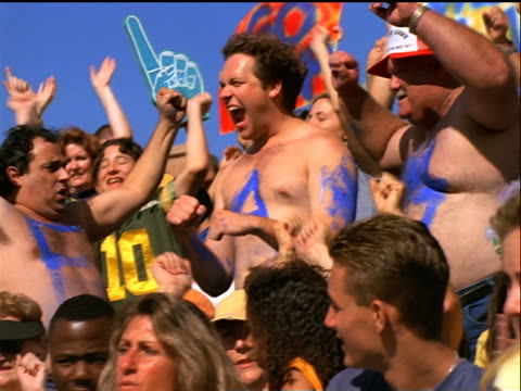 low angle men with letters painted on stomachs bumping stomachs + cheering in crowded stadium - 1999 stock videos & royalty-free footage
