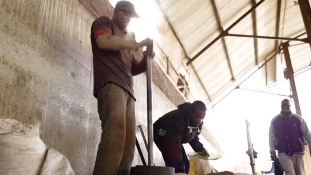 low angle mid shot, joseph khomalo and rafael artas use metal mortars and pestals to smash and sieve medicinal roots that can be boiled into a broth... - broth stock videos & royalty-free footage