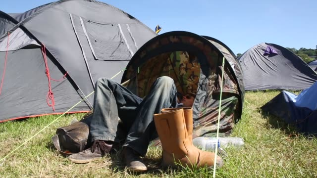 Low angle mid shot of a man sleeping in a tent